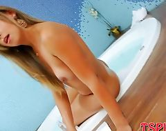 Blonde tranny Caroline Ponciano handjobs cock in jacuzzi
